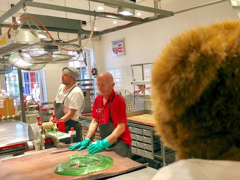 Der Urlaubär schaut den Köchen bei der Herstellung von Bonbons zu