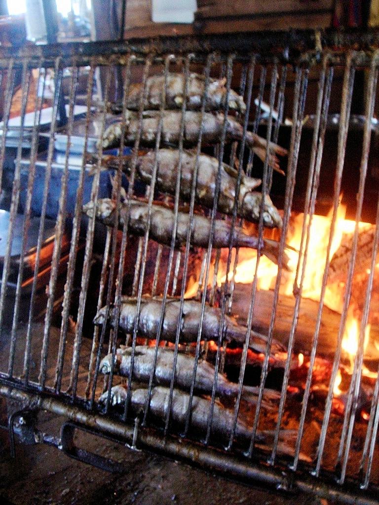 Fische auf einem Wenderost direkt über dem offenen Feuer
