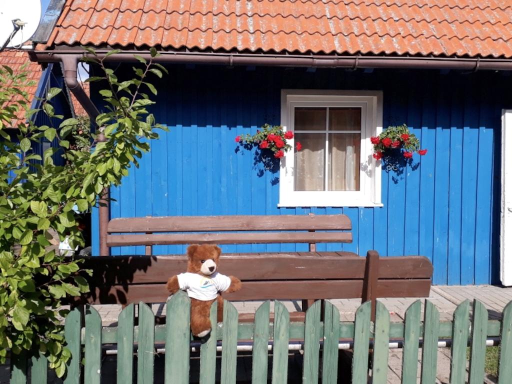 Der Urlaubär vor einem blauem Holzhaus in Nida