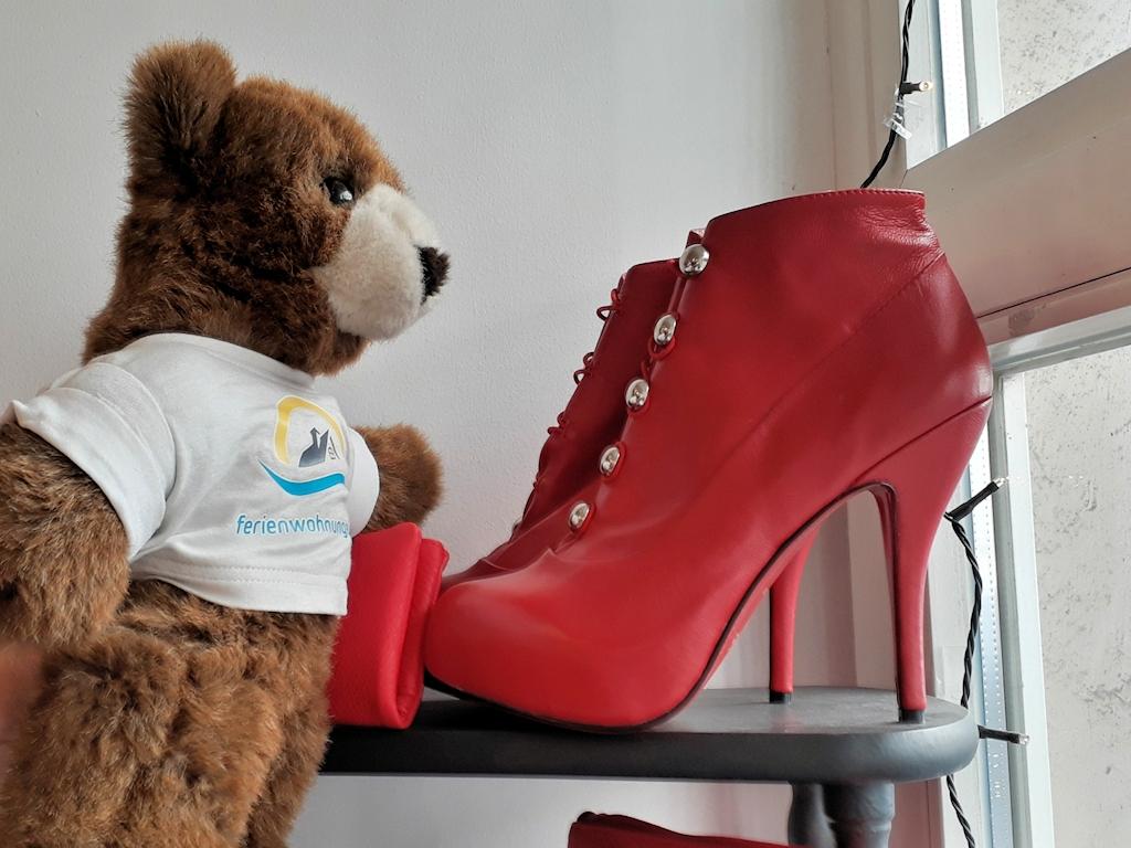 Der Urlaubär bestaunt rote Schuhe