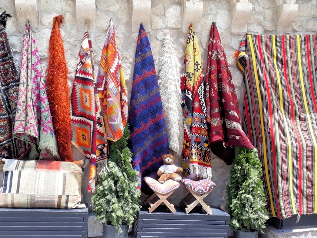Urlaubär vor handgewebten Decken